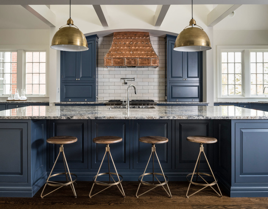 blue cabinetry in kitchen with antique brass pendants