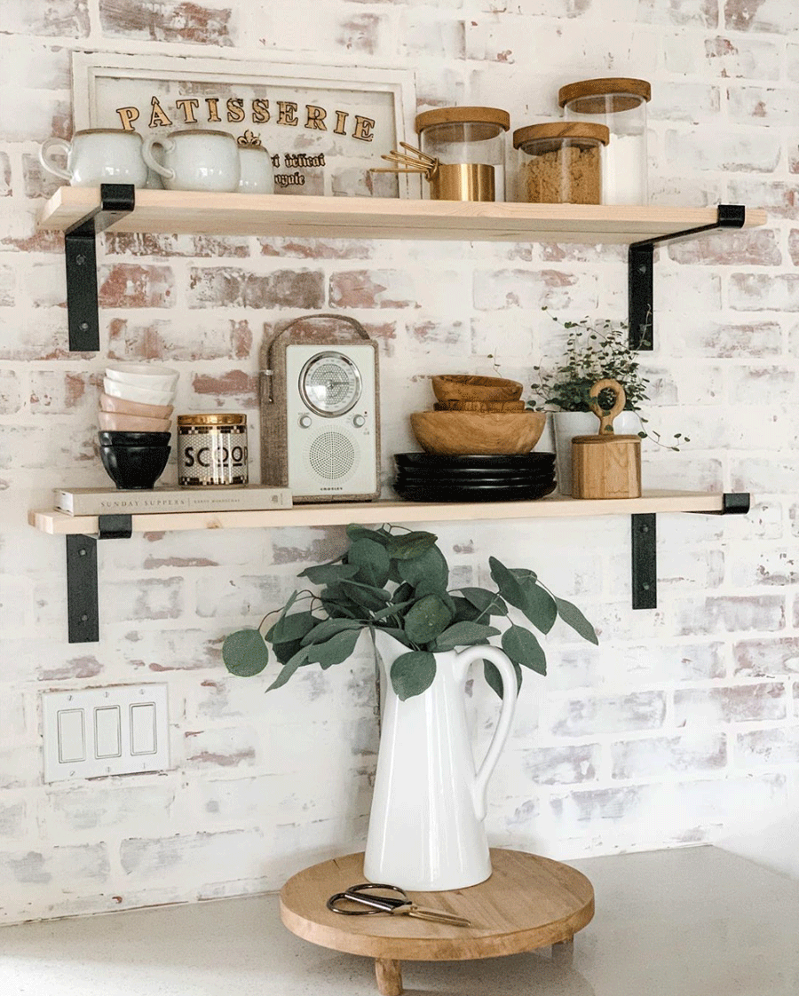 Exposed brick behind open shelving in kitchen.