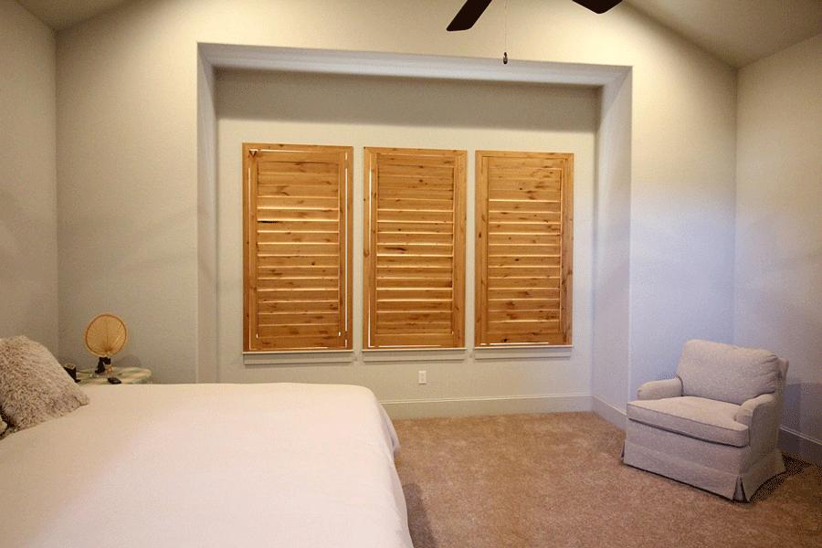 knotty alder wood shutters for room darkening in austin TX bedroom