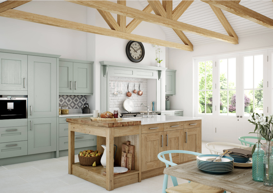 Kitchen with green cabinets and warm wood tones.