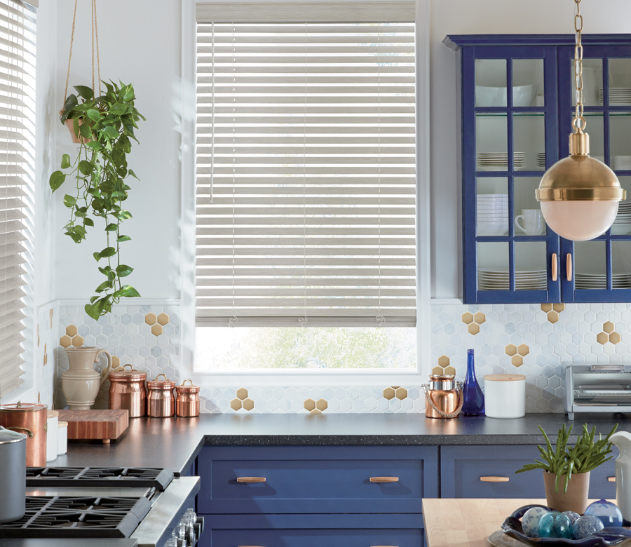 white faux wood blinds in blue kitchen Austin TX