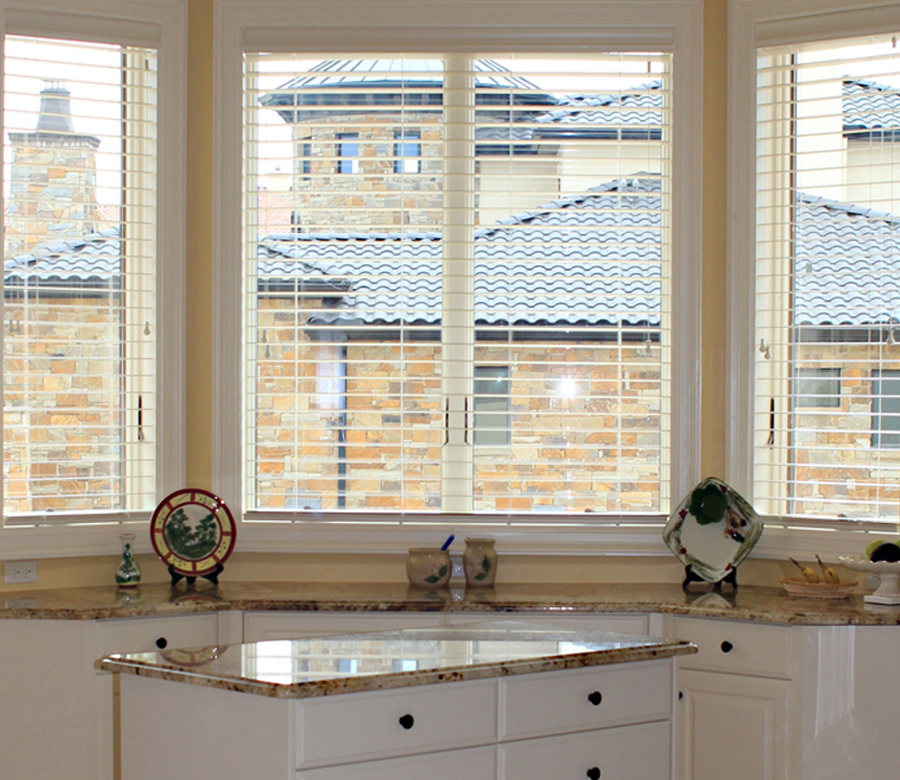 bay windows in Austin TX kitchen with white blinds open for view through