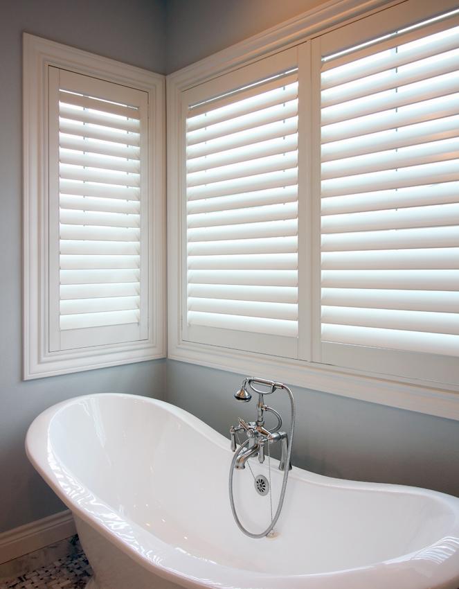 bathroom stand alone tub with large windows white plantation shutters Austin TX