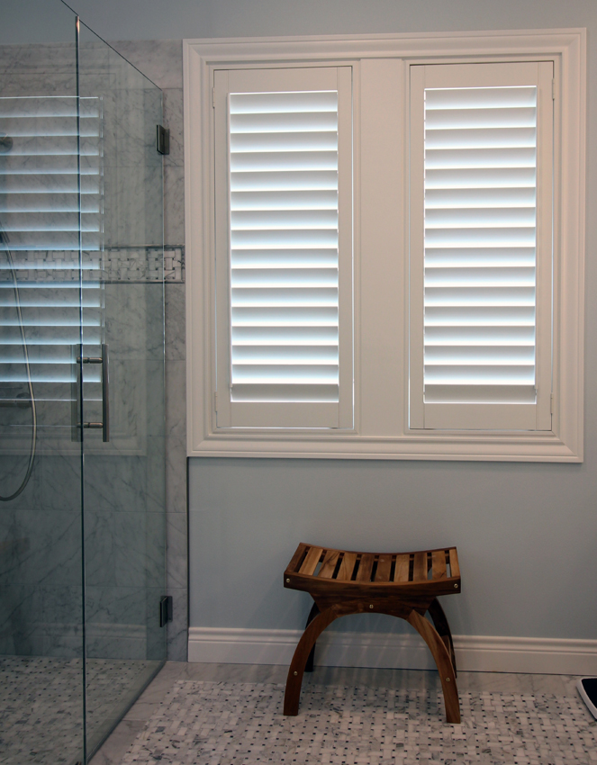 bathroom with natural wood bench plantation shutters Austin 78758