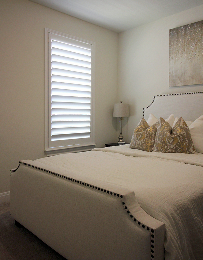 gold master bedroom with white planation shutters Austin 78738