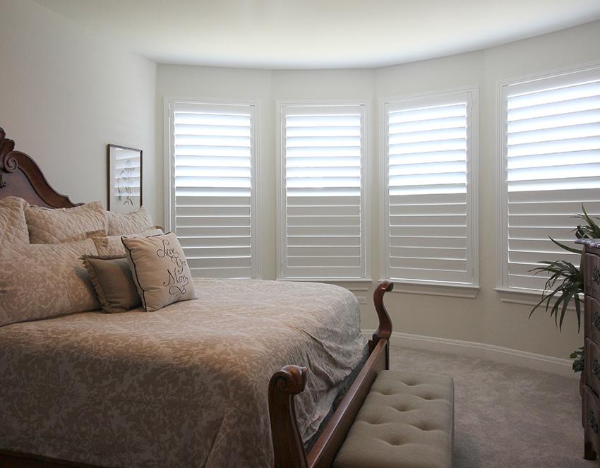 white plantation shutters half opened in master bedroom Austin