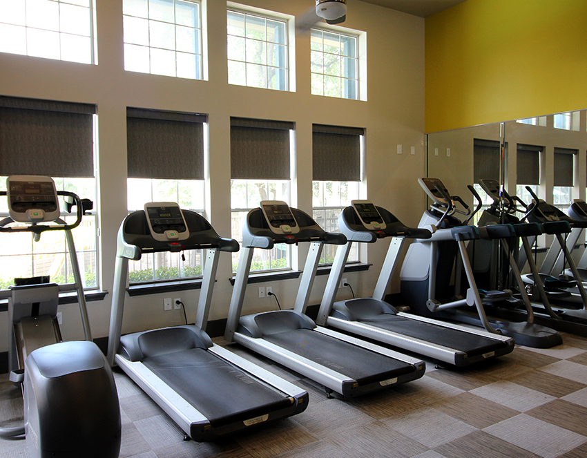 workout space with treadmills roller shades for light control Austin TX