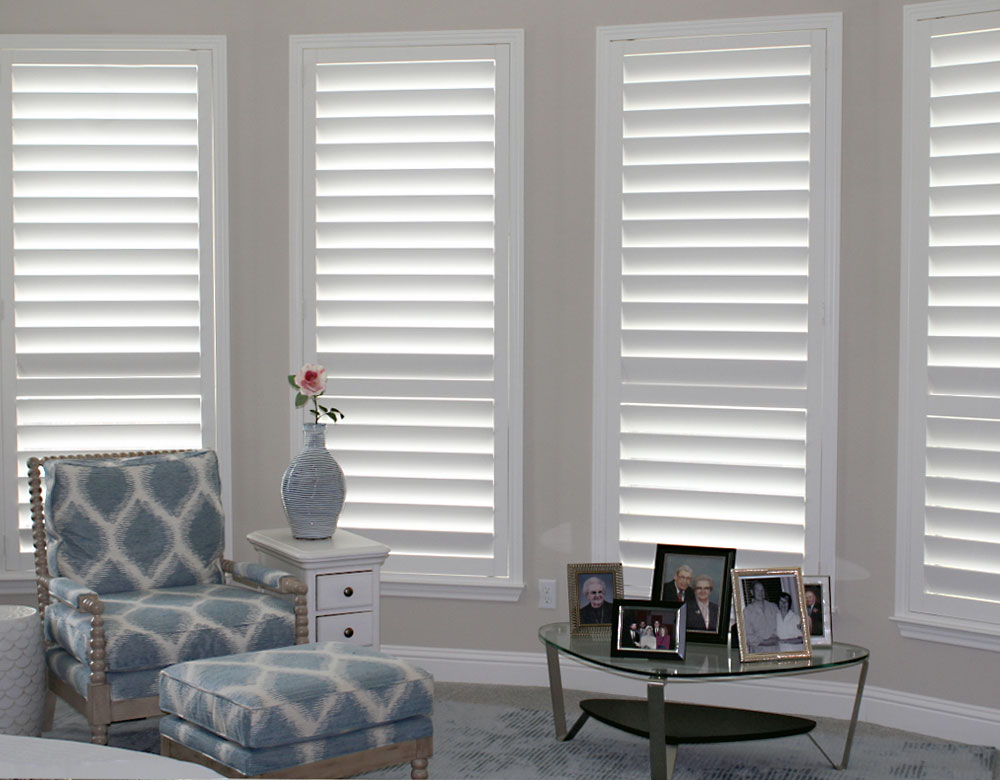 wall of windows covered with white plantation shutters in Austin TX home