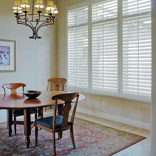 wall of windows with front tilt wood shutters in Austin TX
