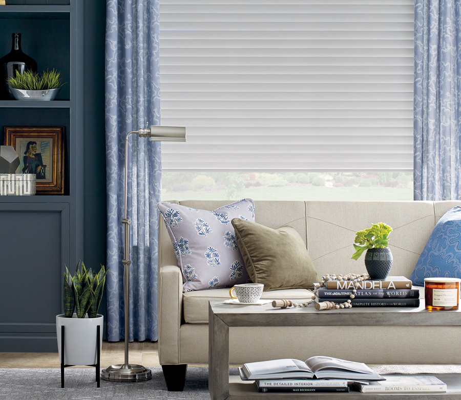 soft blue patterned drapery panels with white window shades in Austin TX living room