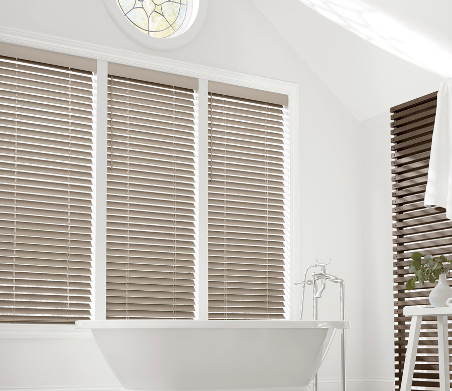 three windows above tub with bathroom window coverings faux wood blinds in Austin TX