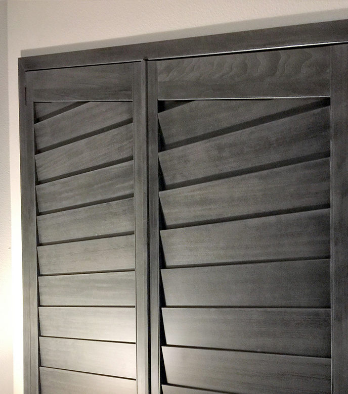 gray stained shutters on angled windows in bedroom in Austin TX