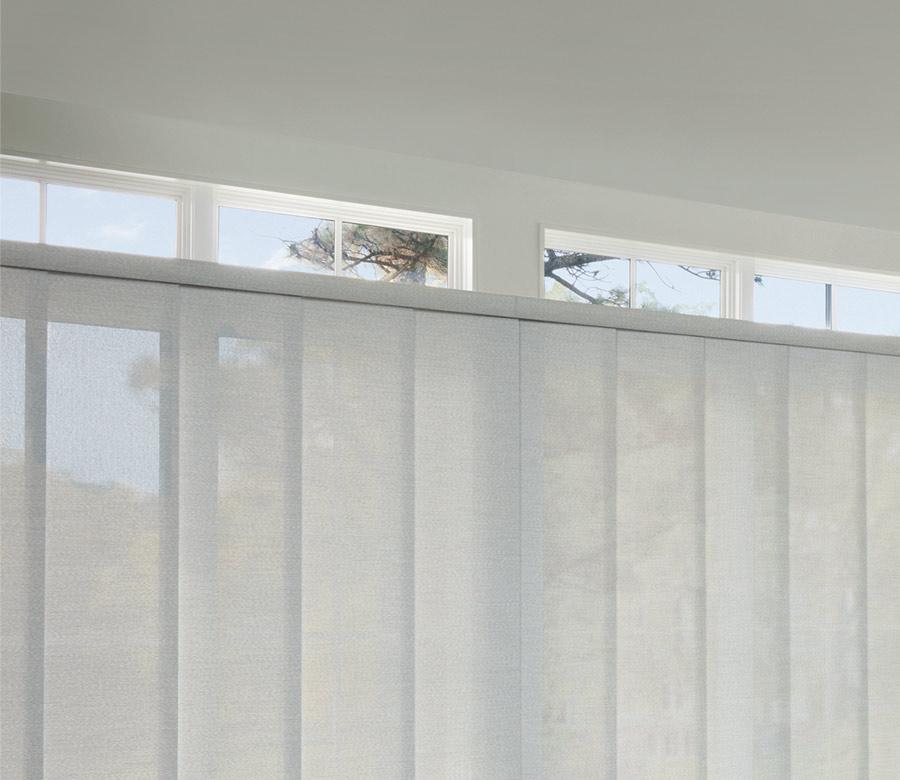gray panel track blinds across large windows in Austin TX