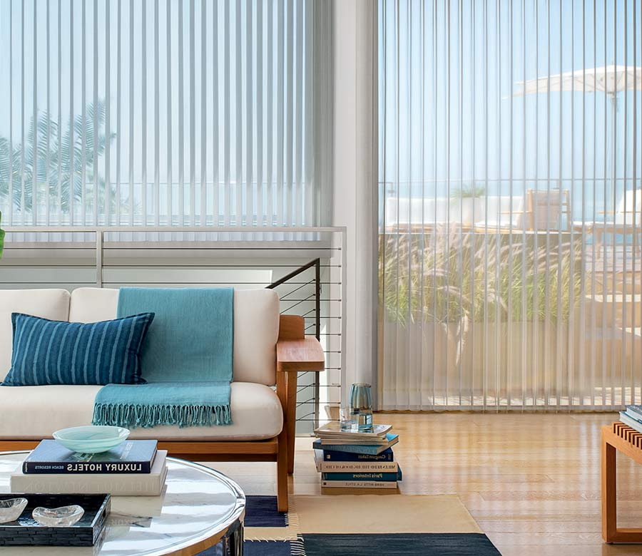 coastal inspired living room floor to ceiling gray window shadings and blue accents in Cedar Park 78613