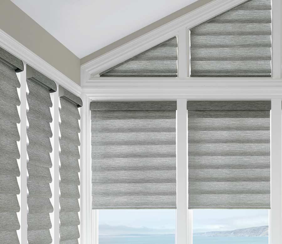 grey roman shades framed by white beams in corner window